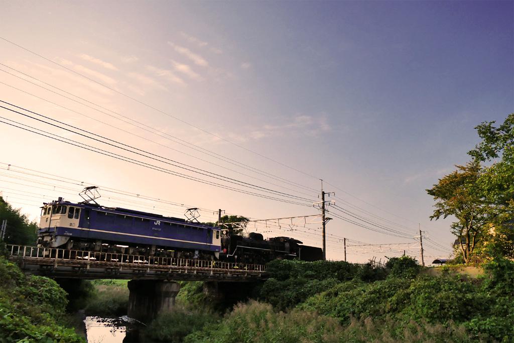 長慶公園から見る蒸気機関車C57-1とEF65-1135の写真素材